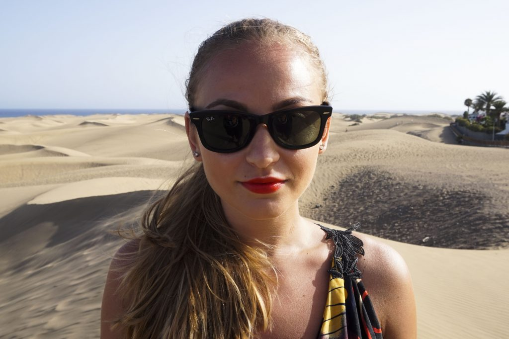 Close of with rayban sunglasses and red lipstick in the sand dunes of Maspalomas Gran Canaria