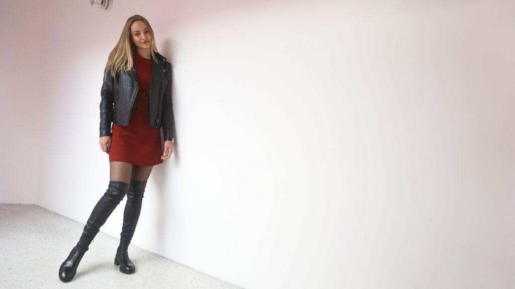 leaning against the wall with diesel leather jacket flared sleeves dress and black leather over knees boots